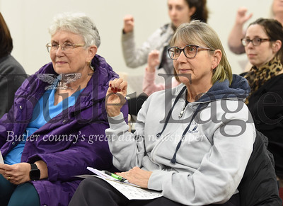 Lisa Szakelyhidi (right) of Harmony, Diane Sims (right) and other area residents practice signing the alphabet at Monday night's introduction to sign language put on by the Cranberry YMCA at the Zelienople Library. Seb Foltz/Butler Eagle 01/14/20