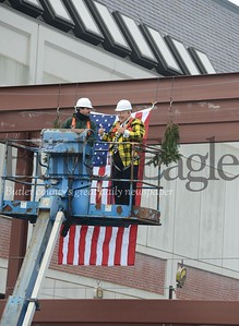 66351 Dale pinkerton hangs flag and decoration up on new building steel