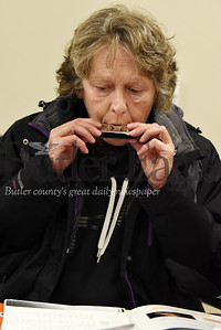 Harold Aughton/Butler Eagle: Terri Dawes of Butler and an Army veteran learns to play the harmonica during the a class to help verterans combat the effects of COPD.