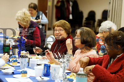 Peggy Kratz(center) of Cranberry and other senior center members chat over lunch at the Cranberry Township Senior Center Winter Blues Party Thursday. Seb Foltz/Butler Eagle