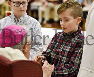 Harold Aughton/Bulter Eagle: Gabriel Kappler, 3rd grader at Butler Catholic, hands the wine to Bishop Zubik prior to Communion Monday afternoon, January 27, 2020.