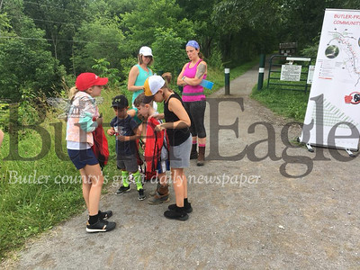 3 column photo. The Soles prepare their children for the Meet Mark's Friends at the Butler-Freeport Community Trail. The children were friends with Mark Fike, an 11-year-old who was killed in a January accident and loved insects. Photo by Nathan Duke.