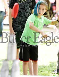 Harold Aughton/Butler Eagle: Nemesio Guzman, 11, of Butler, takes a shot at knocking over the bottles during the carnival held at Rotary Park, Friday, June 28.