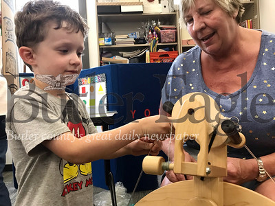 Will Pyda, 4, of Harrisville, touches the wool that Ann Malick, of Zelienople and Butler Spinners and Weavers Guild and Harmony Weavers Cabin member, spun. Photo by Gabriella Canales.