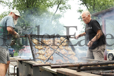 Jim Pritts (left) and Joe Tobin flip grilled chicken on Nixon United Methodist Church's massive grill trailer during the church's annual chicken barbecue. Organizers typically grill 400 half-chickens. Proceeds from the event are distributed by the Methodist Men organization, which puts on the event, and go to local outreach for needy families and area youth. Seb Foltz/Butler Eagle   annual chicken barbecue. Come feast on barbecued chicken, side dishes, drink,and dessert.