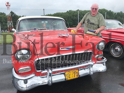 People cleaned the rain off their cars after Saturday's showers at the 19th annual Mega Cruise hosted by the Penn Township Volunteer Fire Department at the Pittsburgh-Butler Regional Airport. Photo by Gabriella Canales.