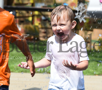 Harold Aughton/Butler Eagle: Levi Neely, 3, of Butler runs through the water compliments of the Butler firefighters during the activities held Tuesday afternoon at the Stuff A Bus event sponsored by the Golden Tornado Scholastic Foundation.