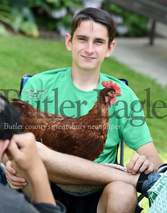 """Harold Aughton/Butler Eagle: Andrew Costel, 16, of the Butler 4-H brought his Rhode Island Red chicken named """"Rhody"""" to the Stuff A Bus event sponsored by the Golden Tornado Scholastic Foundation."""