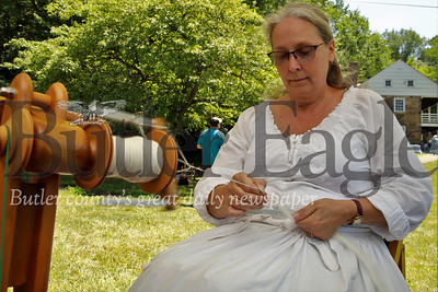 Jean Chestnut spins wool into yarn during Early American Day at the Old Stone House Saturday. Seb Foltz/Butler Eagle