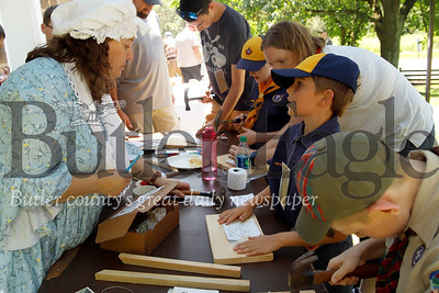 Gabe Kappler gets tin punching instructions from Old Stone House volunteer Stacie Williams during Early American Day at the historic Slippery Rock site. Seb Foltz/Butler Eagle