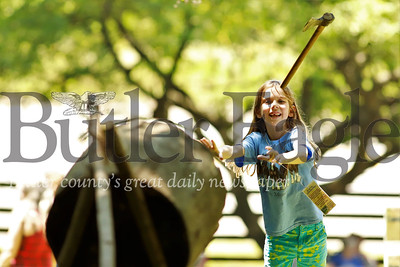 Abby Smith tosses an axe at a log target during Early American Day Saturday at the Old Stone House in Slippery Rock. Seb Foltz/Butler Eagle
