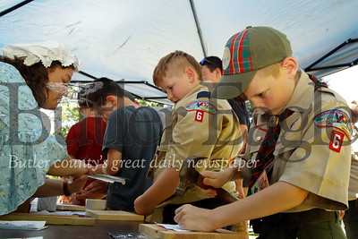 Boy Scout Jackson Jingling, 10, works dilligently at on his tin punching project during Early American Day at the Old Stone House in Slippery Rock. Seb Foltz/Butler Eagle