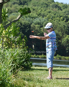 Harold Aughton/Butler Eagle: Cheryl Weir, 74, of Butler reels in one of several blue gill fish she caught Monday moring off the shore at Lake Arthur.