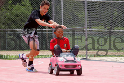 Vinny DePaula, 13, of Cranberry pushes Jeremiah Barjolo, 8, of Zelienople in Barjolo's sister's toy car following basketball camp at Zelienople Community Park Tuesday. Seb Foltz/Butler Eagle 07/23/19