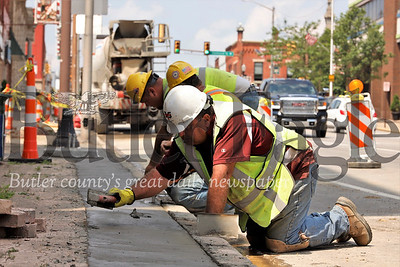 Construction crews smooth freshly poured cement along Main St. in Butler. The Main St. project includes installing underground electric lines and street lighting connections.Work is expected to continue into late in the year according to workers on site. Seb Foltz/Butler Eagle