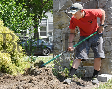 Harold Aughton/Butler Eagle: Ray Dean III works on preparing the mulch beds at the West Sunbury veterans memorial as part of his Eagle Scout project. Thursday, June 2, 2020.