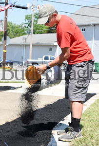 Harold Aughton/Butler Eagle: Ray Dean III distributes a bucket of mulch at the West Sunbury veterans memorial. Dean is working on his Eagle Scout project with his dad, Ray Dean, Jr.