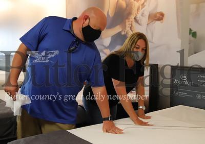 Bryan and Mandy Greenawalt test the firmness of a mattress at Levin Furniture Thursday. Seb Foltz/Butler Eagle