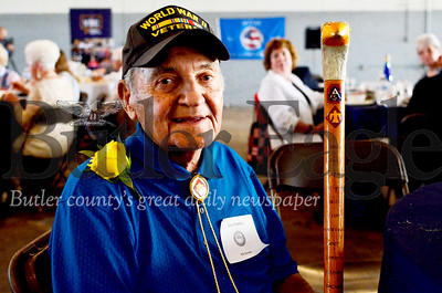 WWII veteran Guy Prestia, 97, sits at a mock USO show at the Pittsburgh-Butler Regional Airport. Prestia was a member of the 45th Infantry Division, the Thunderbird Division. The staff he held has the names of places the war took him inscribed on its side. Tanner Cole/Butler Eagle