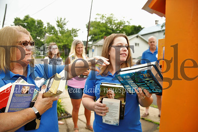 Amy Rubinosky (right) and Nancy Miller load books into the new book boxes in Evans City by th EDCO Park Pool. Seb Foltz/Butler Eagle