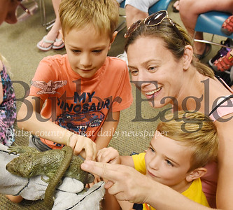 Harold Aughton/Butler Eagle: Melanie Kovach of Butler and her two sons, Lian, 7, (left) and Adin,4, meet animal ambassador, DeWight, a prehensile-tailed Skink, at the Butler Library, Wednesday, June 26.