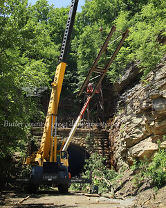 Construction crews lift a section of a steel drainage sluice being installed above the Armstrong Trail tunnel Wednesday 06/17/20. Seb Foltz/Butler Eagle
