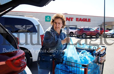 Ruth Schmidt of Renfrew loads groceries into her car at the Moraine Pointe Plaza Giant Eagle Friday. Schmidt said she and her husband were out for their usual grocery purchases and did not stock up on any additional supplies, given nationwide concerns for the Covid 19 outbreak. Seb Foltz/Butler Eagle