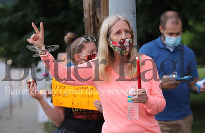 A protestor in Zelienople raises a piece sign to passing motorists. Seb Foltz/Butler Eagle
