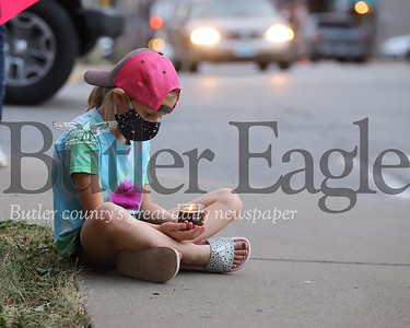 Adele Troyan of Evans City sits looking at her candle during a moment of silence at Wednesday evenings protest in Zelienople. Seb Foltz/Butler Eagle