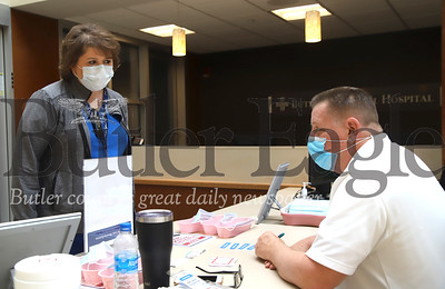 Butler Memorial Hospital clinical supervisor Triscia Bartley simulates checking in for her shift with check-in attendent Howard McCormick Thursday. Seb Foltz/Butler Eagle