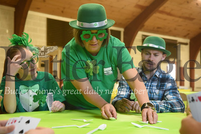 Moniteau Junior and Senior High School seventh-grader Jaycee Relihan and Matt Wallace, of Robinson, wait for Christ Community United Methodist Church youth director Cherie to place spoons on the table for the church's St. Patrick Game Night on Sunday.