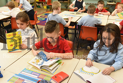 Harold Aughton/Butler Eagle: Butler Catholic first graders (left - right) SOphia Stegner, Lucas Stewart, and Elyn Kearns take part in National Read Across America day in Mr. Brian Herlihy's class, Monday, March 2, 2020.