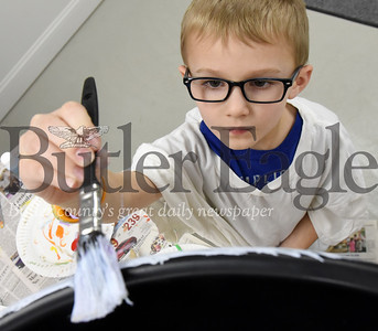 Harold Aughton/Butler Eagle: Jackson Meyer, 6, of Zelienople does his part painting a rain barrerl as part of a class project designed for homeschoolers at the Zelienople Library, Tuesday, March 3, 2020.
