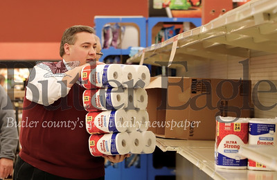 Moraine Pointe Plaza Giant Eagle staff member Brian Lippert restocks toilet paper directly from a delivery truck Friday. Customers were snatching up rolls almost as fast as they were being restocked due to Covid 19 fears. One Giant Eagle official said that while the store as a whole was well stocked, items precautionary items suggested by the media, such as toilet paper and cleaning supplies, were selling the fastest. Seb Foltz/Butler Eagle