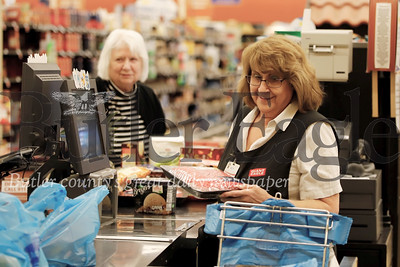 Giant Eagle cashier Betty Graham rings up groceries for Beverly Hazlett-Dambaugh(left) and Jerry Dambaugh Friday at the Moraine Pointe Plaza Giant Eagle. Hazlett-Dambaugh said they were stocking up a little extra on certain groceries, as a precaution given Covid 19 news. Seb Foltz/Butler Eagle