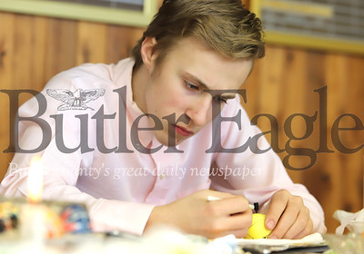 """Seth Prokopchak uses  a wax pen called a """"kitstka,"""" to draw on his  Ukrainian Pasaky egg. The process involves dying eggs multiple colors using wax layers to keep dye from reaching certain parts of the egg. Seb Foltz/Butler Eagle"""
