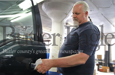 Butler County Ford detailing manager Jeff Christy wipes down the door handle on a new Ford truck with a Lysol wipe. Seb Foltz/Butler Eagle