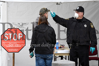 Harold Aughton/Butler Eagle: An officer from the Butler County Sheriff's department checks the tempature of individuals prior to entering the court house Thursday, March 19, 2020.
