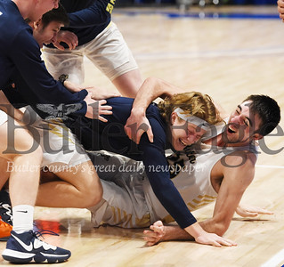 Harold Aughton/Butler Eagle: Butler boys basketball team tackles senior standout Ethan Morton after winning the WPIAL Class 6A championship game against Mt. Lebanon, Saturday, Feb. 29, 2020.