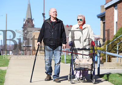 While some seniors remain indoors out of concerns for covid 19, Mary Jo Koch, 86, of Butler chose to enjoy the sunshine and walk to the downtown Saint Vincent de Paul to deliver her food donations Thursday.  Koch ran into friend Ron Seezox (left) who joined her on the walk.