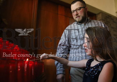 Reagan Large, 8, of Butler lights a prayer candle with her father Tom Large Thursday at St. Fidelis Roman Catholic Church in Meridian. Seb Foltz/Butler Eagle
