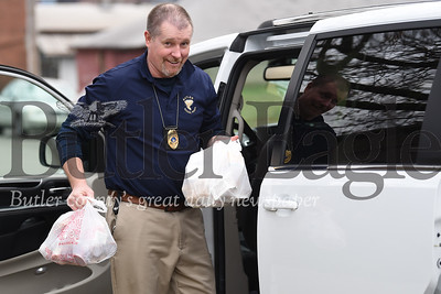 On Friday, March 27,2020, members of Butler Area School District's school police officers took to the streets of the district to delivery food to students in need at their homes. Pictured is Gary Thompson dropping off bags of food along Negley Avenue in the Island neighborhood.