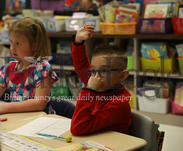 McQuistion Elementary first grader Elijah Snyder (right) raises his hand to share Mother's Day letter idea. Maddalyn MConahy also pictured. Seb Foltz/Butler Eagle