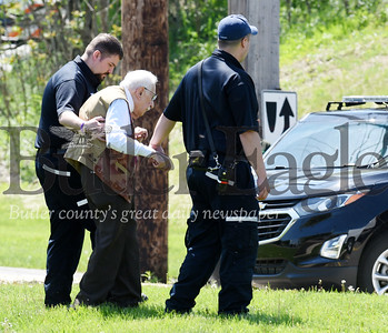 Harold Aughton/Butler Eagle: Emergency personnel escort a victim of a car crash at the intersection of Rt. 228 and Valencia roads to a nearby ambulance for observations Monday, May 6.