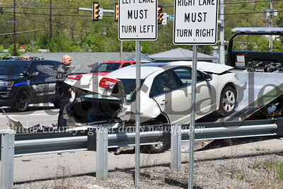 Harold Aughton/Butler Eagle: An Adams Twp. police officer watches as a toe truck driver removes one of the cars involved in an accident at the intersection of Valencia and Rt. 228, Monday, May 6.