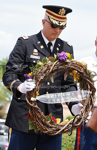 Harold Aughton/Butler Eagle: Alex D. Barna places a wreath in memory of those who served in the Marine Corp. during the Memorial Day ceremony held at the North Boundary Park in Cranberry Twp. Sunday, May 26.