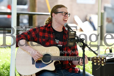 Harold Aughton/Butler Eagle: Butler resident, Zach Rovito of the band Hawkeyes, strums his guitar to Tom Petty's American Girl, on the opening day of the City of Butler Farmers' Market, Saturday, May 25, 2019.