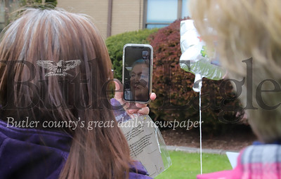 Peggy Wilson (left) and family friend Bev McCanch talk to Wilson's mom Carol Shaw via Facetime at Sunnyview Nursing and Rehabilitation Center. Friends and family gathered outside the facility with signs wishing Shaw a happy 82nd birthday. Shaw was able to wave from a second story window. Seb Foltz/Butler Eagle