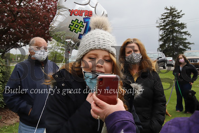 Caitlin Shaw talks to her grandmother Carol Kremer via Facetime outside of Sunnyview Nursing and Rehabilitation Center Sunday. Family gathered outside of the facility to celebrate Kremer's 82nd birthday. Kremer watched and waved from a second story window of the building which has been on lockdown since the start of the COVID-19 outbreak. Seb Foltz/Butler Eagle