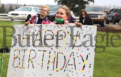 Mallory Collins holds up a sign for her great aunt Carol Kremer's 82nd birthday at Sunnyview Nursing and Rehabilitation Center Saturday. Family gathered outside with signs while Kremer waved and communicated via Facetime from a second story window. Seb Foltz Butler Eagle